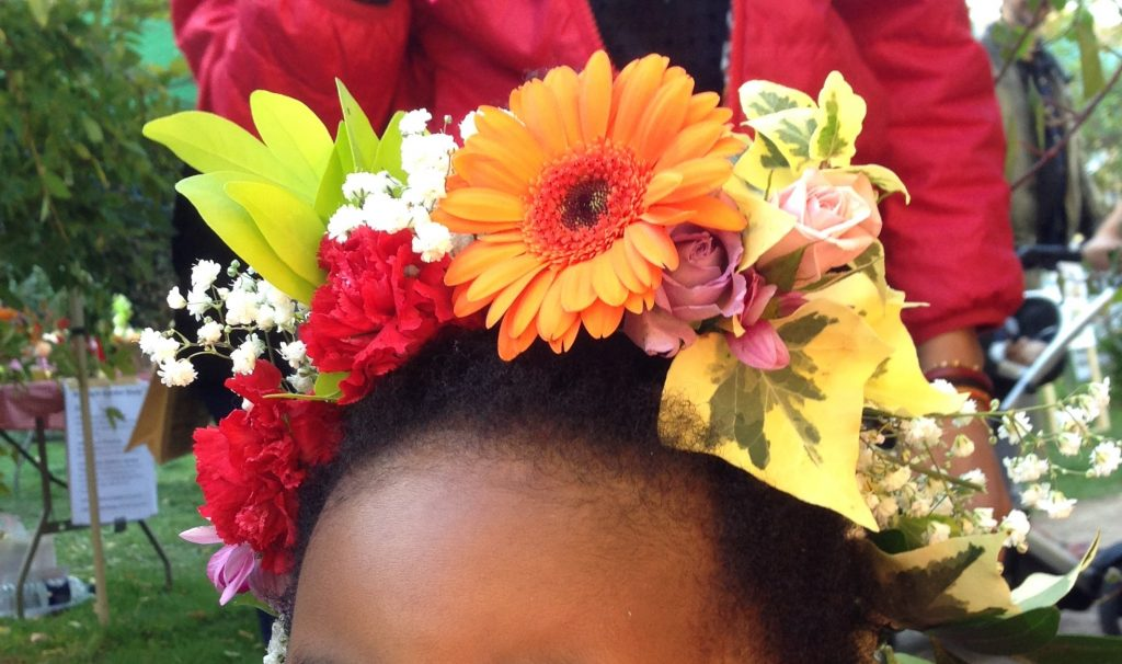 Floral crown featuring orange gerbera, pink roses, variegated ivy, gypsophila and carnations and